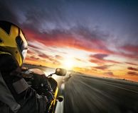 Two motorbike`s riders heading to the city. Concept of speed, tr. Avel and freedom. Beautiful dramatic sunset sky Royalty Free Stock Photos