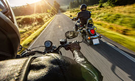 Two motorbikers riding on empty road. With sunrise light, concept of speed and travel in nature Royalty Free Stock Photo