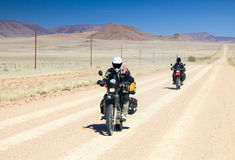 Two motorbikes driving fast on long straight desert road. Royalty Free Stock Photo