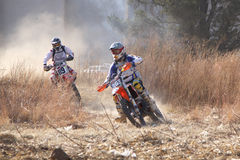 Two motorbikes kicking up trail of dust on sand track during ral Stock Photos
