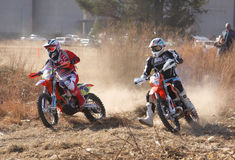 Two motorbikes kicking up trail of dust on sand track during ral Royalty Free Stock Images