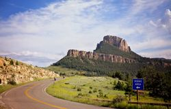 Mountainous landscape with a winding highway. Two motorbikes travelling along a winding highway between mountains in a summer landscape in a Wyoming landscape royalty free stock images