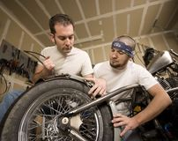 Two Motorcycle Mechanics Placing a Fender Royalty Free Stock Images