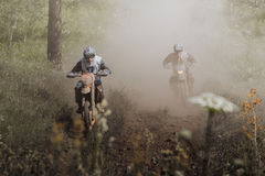 Two motorcycle riding. On forest dusty trail Royalty Free Stock Photography
