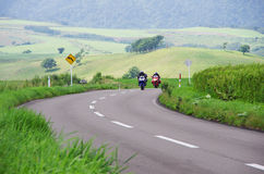 Two motorcycles coming to a corner. On a hill Royalty Free Stock Photo