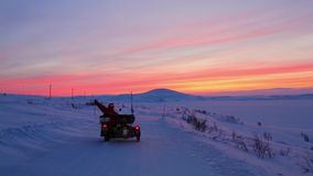 Two motorcycles with sidecars ride along snow-covered road far beyond Polar Circle against backdrop of scarlet sunset stock footage