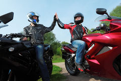 Two motorcyclists greetings on country road. Summer stock photos