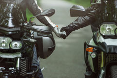 Two motorcyclists are holding hands while sitting on motorcycles. A man and woman in love, a common hobby Royalty Free Stock Photos