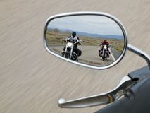 Two motorcyclists in the rearview mirror stock image