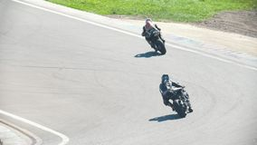 Two motorcyclists in the race, turn to the left, slow-motion. Telephoto shot stock video