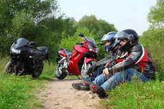 Two motorcyclists sitting on country road Royalty Free Stock Image