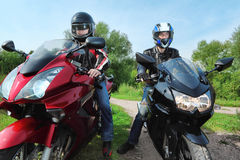 Two motorcyclists standing on country road. Summer stock images