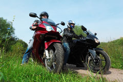 Two motorcyclists standing on country road Royalty Free Stock Photos