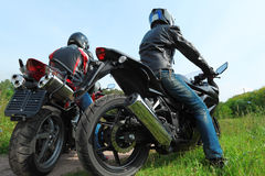 Two motorcyclists standing on country road Royalty Free Stock Image