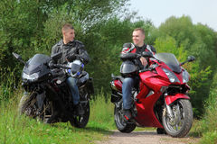 Two motorcyclists standing on country road royalty free stock images