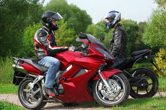 Two motorcyclists standing on country road Stock Image