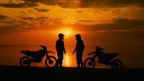 Two motorcyclists at sunset communicate. They are naberegu River, near his motocross bike. stock footage