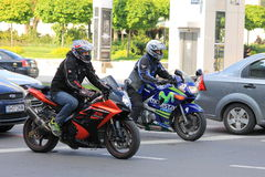 Two motorcyclists in traffic. A view with two motorcyclists in traffic starting at green light at the semaphore Stock Photo