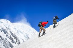 Two mountain backpackers walking on steep hill with snowed peaks background, Himalayas. Nepal stock images