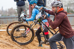 Two mountain bike racers on sand. Mountain bike contest on unfinished construction. First edition of Urban Trail Cross Country Short Circuit - XCC inside of stock photo