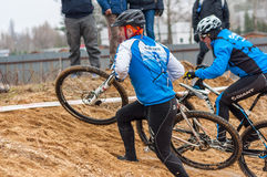 Two mountain bike racers on sand. Mountain bike contest on unfinished construction. First edition of Urban Trail Cross Country Short Circuit - XCC inside of Stock Photos