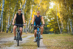 Two mountain bikers riding bike in the forest Royalty Free Stock Photo