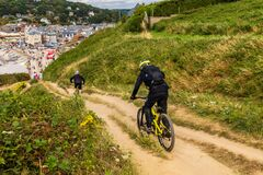 Two mountain bikers wearing safety gears going downhill, Etretat, France