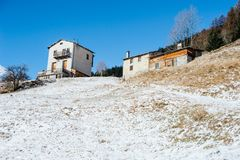Two mountain houses on a snowy slope in blue morning sky. Two mountain houses in the Italian Alps, above a snow-capped slope in the morning blue sky Royalty Free Stock Image