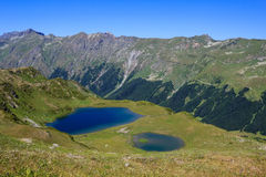 Two mountain lakes surrounded with green alpine meadows and forest Stock Photos