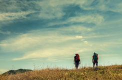 Two mountain travelers with backpacks under blue sky Royalty Free Stock Photos