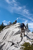 Two mountaineers hiking to the top of the mountain Royalty Free Stock Images