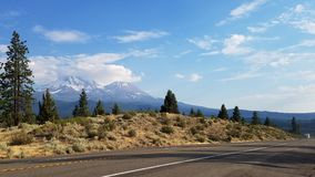 Dual snow capped mountain peaks in the Distance. Two mountains rise up in the distance as the roadway /highway leads us into the distance.  Diagonal Royalty Free Stock Photography