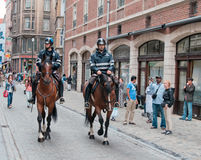 Two mounted policemen patrol the street in center Stock Image