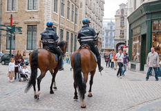 Two mounted policemen patrol the street in center Stock Photography