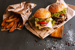 Two mouth-watering, delicious homemade burger. Used to chop beef. on the wooden table Stock Photos
