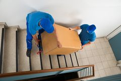 Two Movers With Box On Staircase Royalty Free Stock Photos