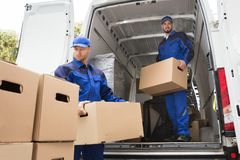 Two Movers Carrying Cardboard Box. Two Young Male Movers Carrying Cardboard Box From Truck stock photos