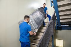 Two Movers Carrying Furniture On Staircase. Two Young Male Movers In Uniform Carrying Furniture On Staircase stock images