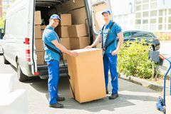 Two Movers Loading Boxes In Truck. Two Happy Movers In Blue Uniform Loading Boxes In Truck Royalty Free Stock Image
