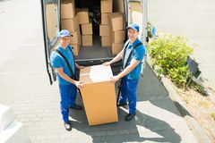 Two Movers Loading Boxes In Truck Stock Images