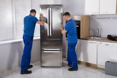 Two Movers Placing Refrigerator In Kitchen. Two Young Male Movers Placing Steel Refrigerator In Kitchen royalty free stock photo