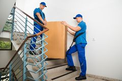 Two Movers Standing With Box On Staircase Royalty Free Stock Photos