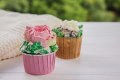 Two muffins with colored butter flowers on white wooden table with bright greens background. Hygge style stock image