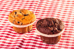 Two Muffins on table. Some delicious homemade muffins with chocolate drops on a red and white checkered tablecloth Royalty Free Stock Images