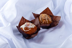 Two muffins on white tablecloth Stock Photos