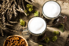 Two mug beer with wheat and hops, basket of pretzels Stock Photography