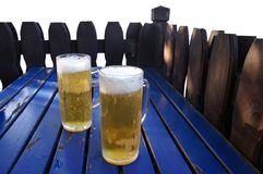 Two mugs of beer. Stand on the wooden table Royalty Free Stock Images