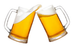 Two mugs of beer with splash. Cheers, two mugs of beer toasting creating splash isolated on white background. Pair of beer mugs making toast. Beer up. Golden Stock Photo
