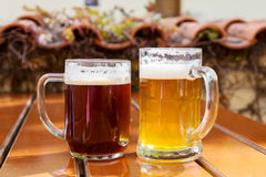 Two mugs of beer on a table at an outdoor cafe Royalty Free Stock Photo