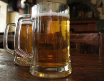 Two mugs of beer on a wooden table Royalty Free Stock Photo